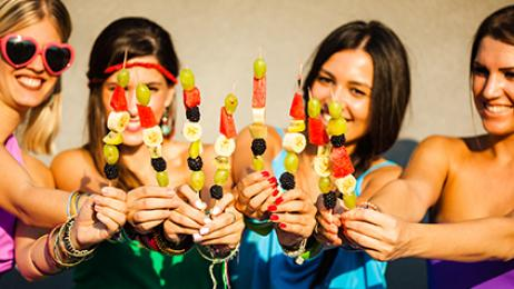 fruitbouquets.com deal tile girls eating fruit kabobs